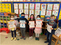 Kindergarten students holding up their